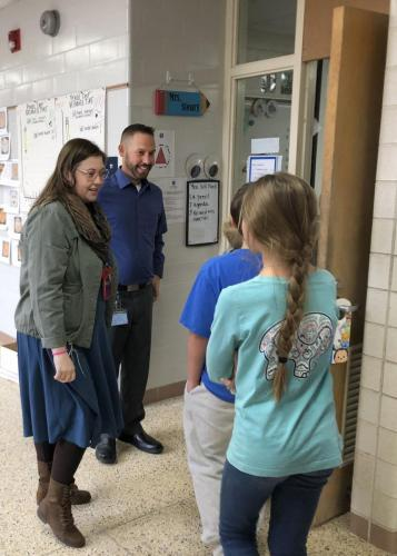 Woman and Man standing. Talking to two students.